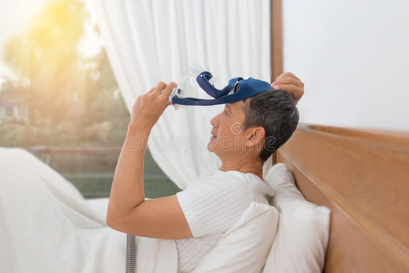 Man lay in bed wearing CPAP mask ,sleep apnea therapy. stock photo