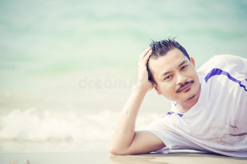 A man laying on the beach and water flow in the summer time. royalty free stock image