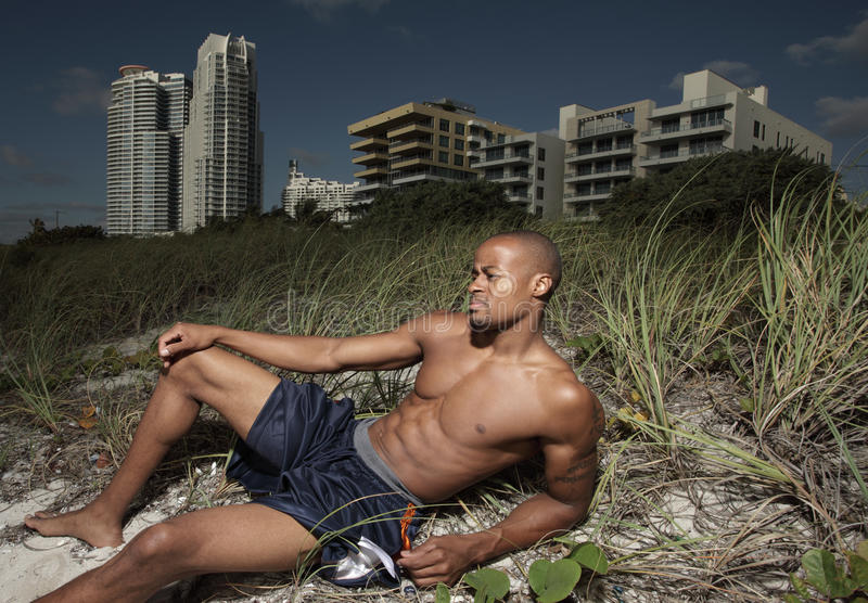 Man laying in the dunes. Handsome man laying in the beach dunes and sunbathing stock images