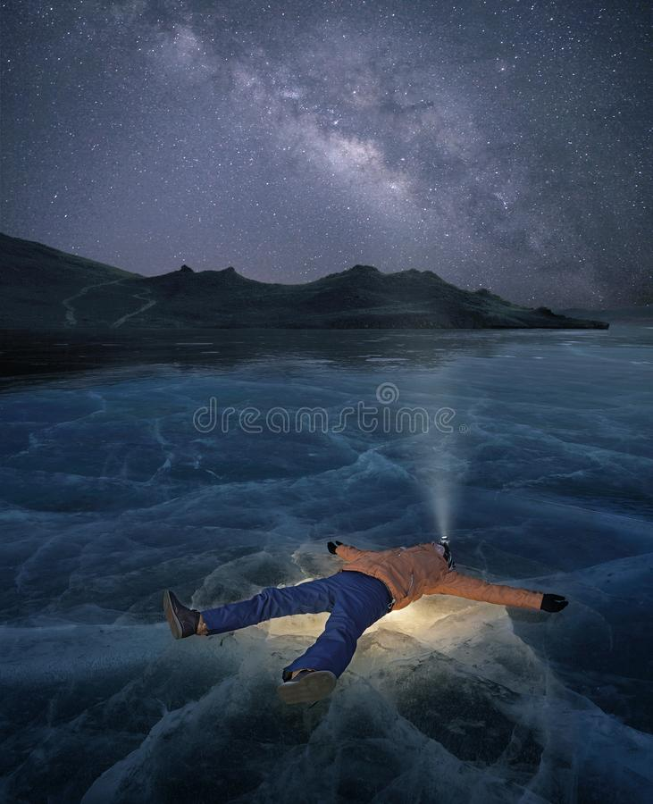 Man laying on a frozen lake royalty free stock photo