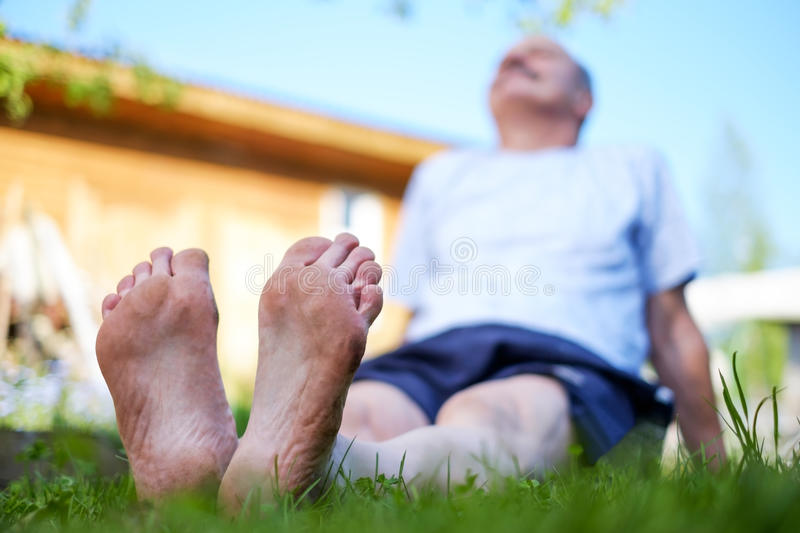 Man laying on grass field. He relax on nature in summer. Look up on sky stock photography