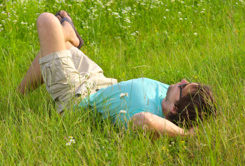 Man laying on grass field Summer day Relaxation. Outdoor Leisure Time on Nature royalty free stock photos
