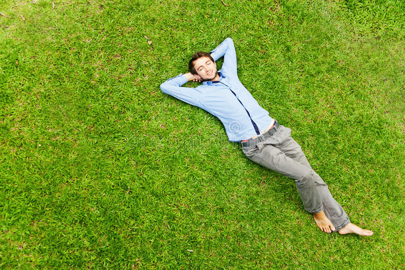 Man laying on a grass stock image