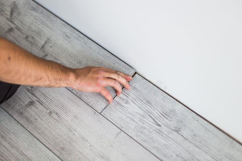 Man laying laminate flooring. closeup on fitting the next piece. Man laying laminate flooring - closeup on fitting the next piece stock photography