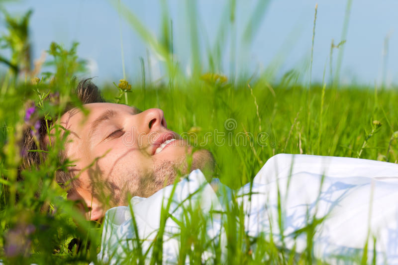 Man laying on a lawn and is dreaming. Young man laying on a lawn or meadow in summer and is dreaming or sleeping royalty free stock photography