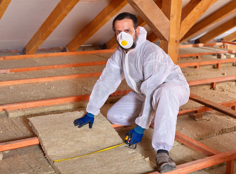 Man laying thermal insulation stock images
