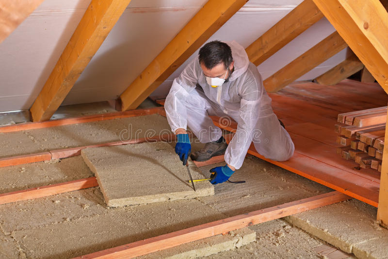 Man laying thermal insulation layer - cutting the panels stock images