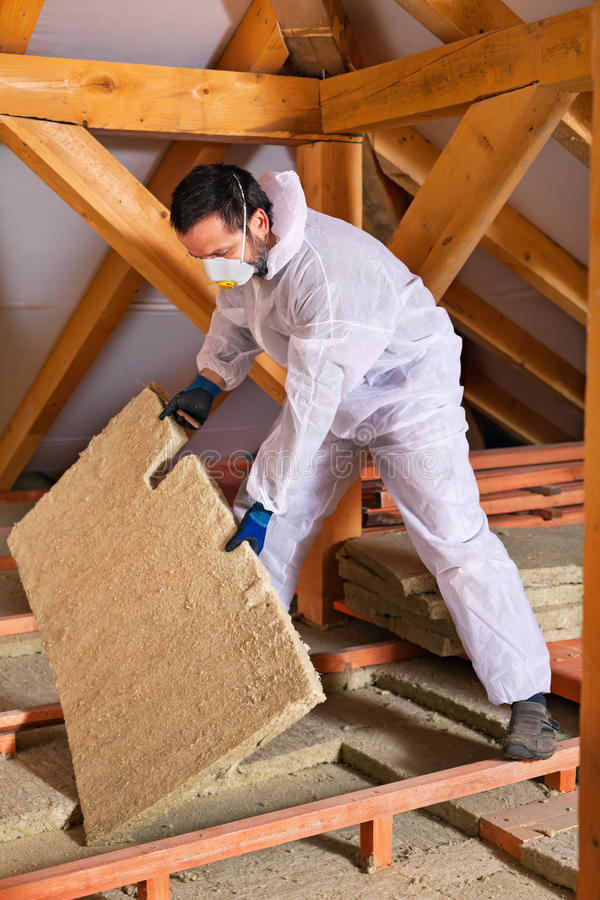 Man laying thermal insulation layer stock photo image for Wool house insulation