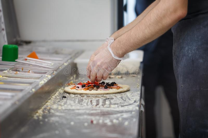 Man lays out ham, olives, paprika, tomatoes and other stuffing on pizza at pizzeria.  royalty free stock photo