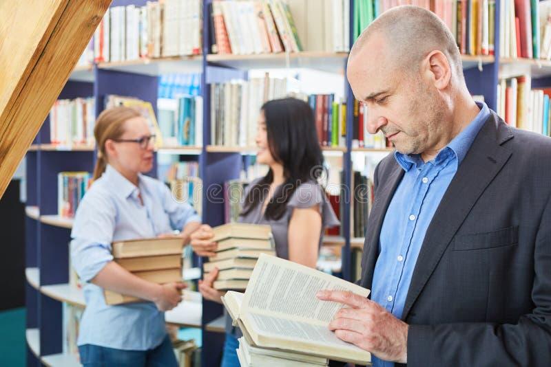 Man leafing through a book in bookstore. Man leafing through a book in a university bookstore or library stock photos