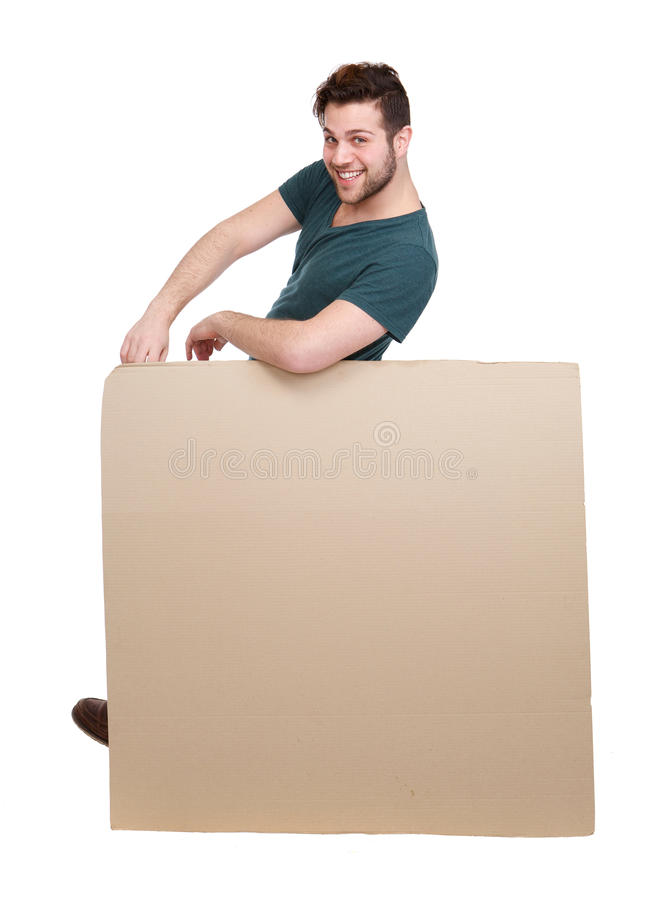 Man leaning on blank poster board. Full length portrait of a happy young man leaning on blank poster board on isolated white background royalty free stock photography