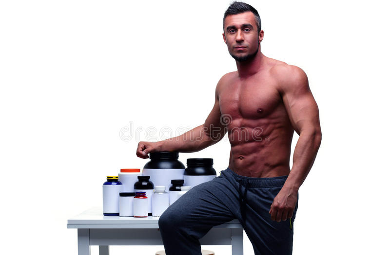 Man leaning on the table with sports nutrition royalty free stock photos