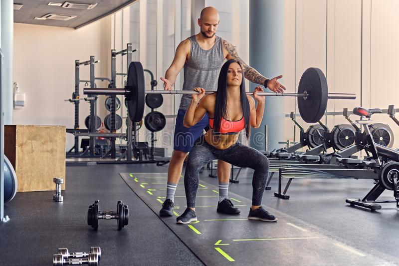 A man learning a woman doing squats. royalty free stock photography