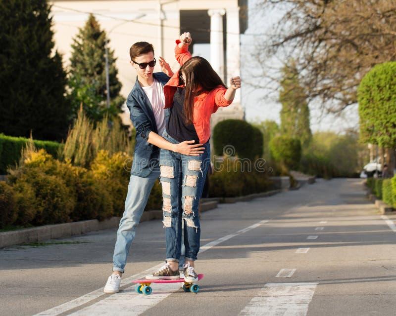 Man learns girlfriend to skateboard stock photography