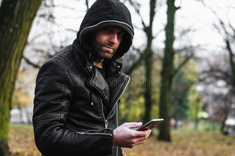 man in a leather jacket with a beard with hood stock photos