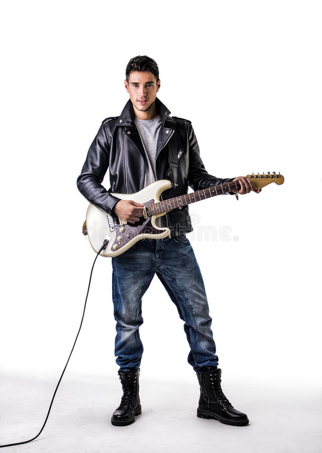Man in Leather Jacket Playing Electric Guitar. Full Length Portrait of Young Man Wearing Leather Jacket and Combat Boots Playing Electric Guitar in Studio with royalty free stock image