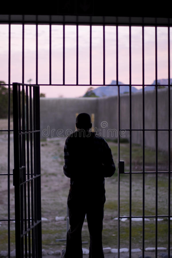Man Leaving Prison. Robben Island, South Africa - August 3, 2008: The outline of a man, at sunset, exiting through the iron bars into the prison yard of a jail stock images