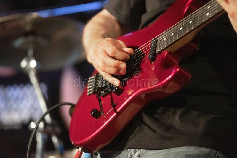 Man ledningsgitarristen som spelar den elektriska gitarren p? konsertetapp royaltyfri fotografi