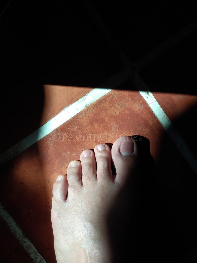 The man left foot on brown tile floor in morning light. royalty free stock photography
