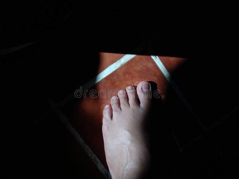 The man left foot on brown tile floor in morning light. stock photo
