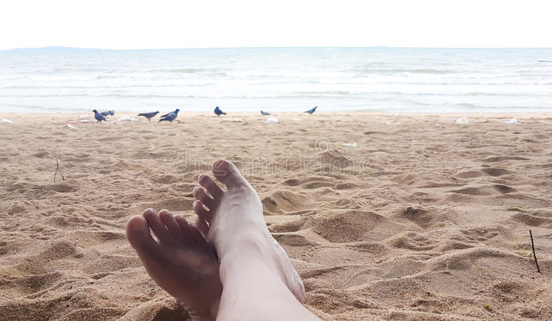Man leg has relax on the sand beach in his holiday. Background stock image