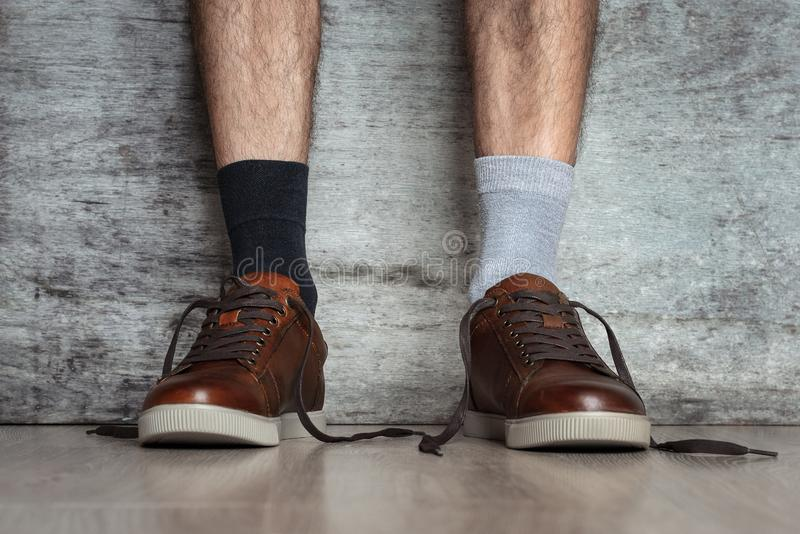 Man legs in brown leather shoes and different socks on a dark background, close up. Concept of strange idiot man stock images