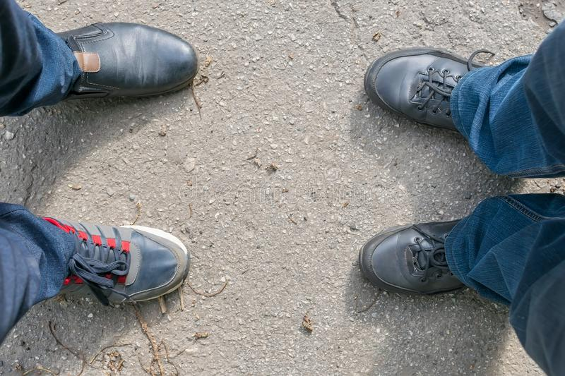 Man legs are mistakenly shod in different shoes. The feet of two men stand on an asphalt road, one guy mistakenly shod in different shoes, shoes and sneakers stock photo