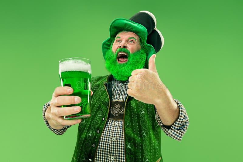 A man in a leprechaun hat at studio. He celebrates St. Patrick`s Day. A smiling happy senior man in a leprechaun hat with green beer at studio. He celebrates St stock photos