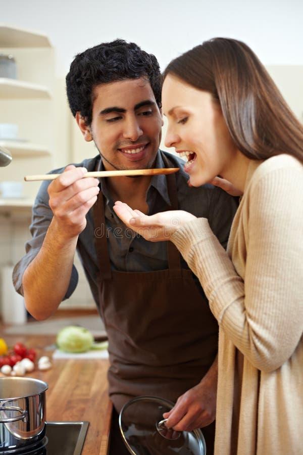 Man letting woman taste soup. Man in kitchen letting woman taste a soup with a wooden spoon stock photo