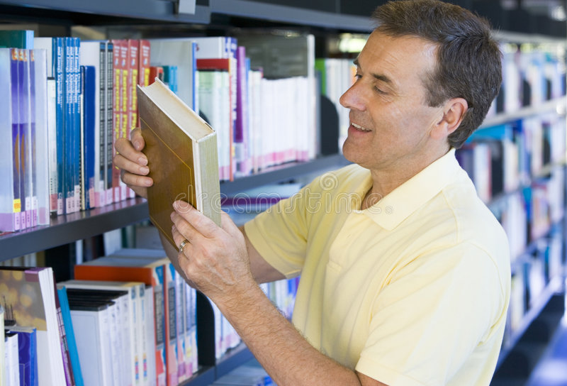 Man in a library reading book cover.  stock photos