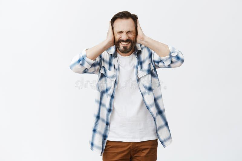 Man lidande från höga stämmor i huvud och att vara misshagit och bedrövligt Bekymrad intensiv vuxen man med sjukdomen arkivfoto