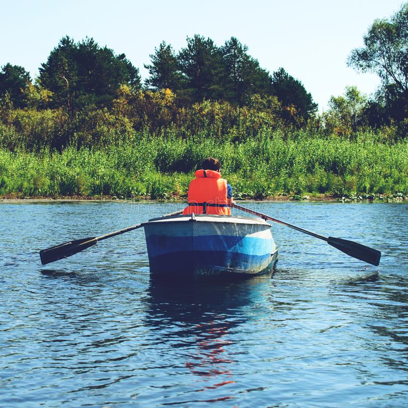Man in life jacket rowing a boat over clear water on the river, royalty free stock photo