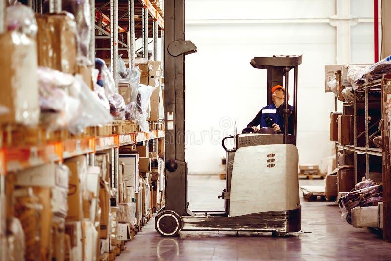 Man on lift operator in uniform at warehouse stock photos