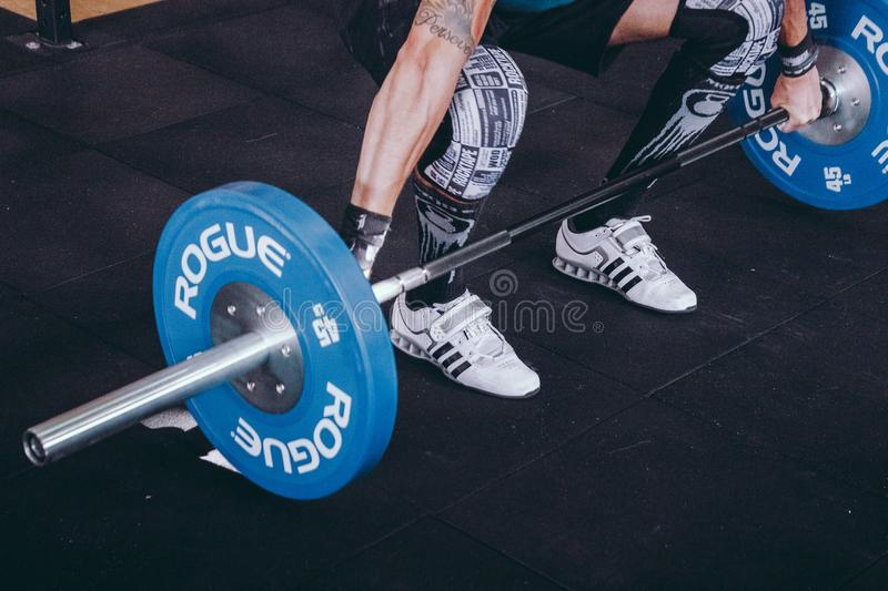 Man With Lift Stance Holds Blue Rogue Adjustable Barbell royalty free stock photos