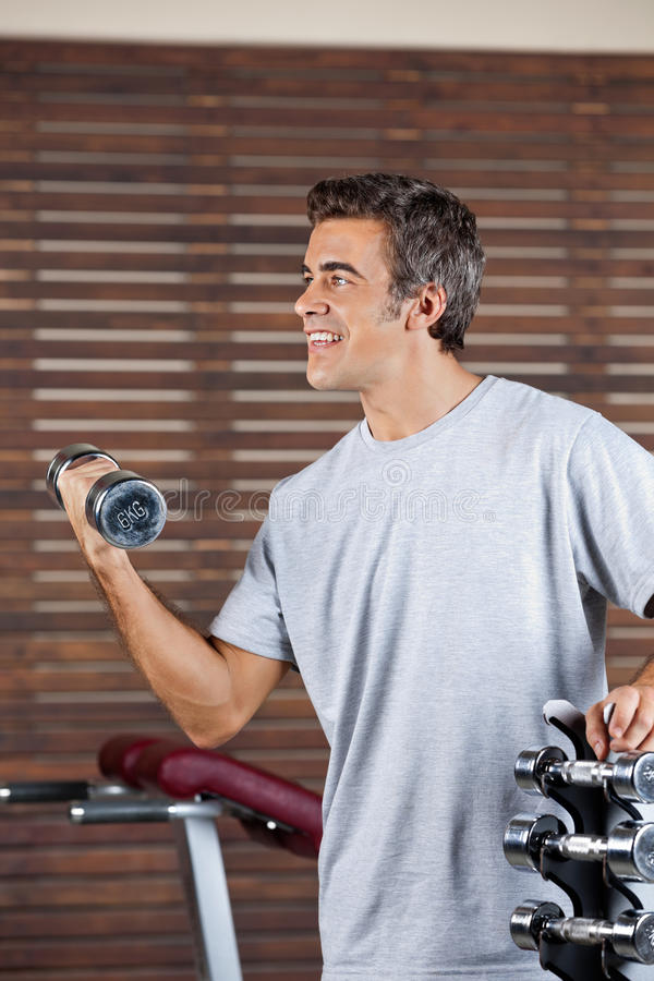 Man Lifting Dumbbell In Health Center stock images