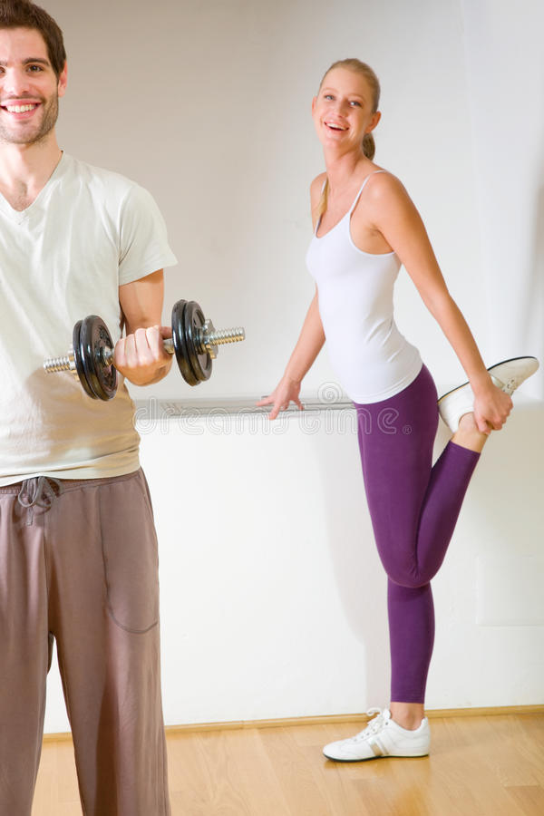 Man lifting dumbbell and woman stretching royalty free stock photography