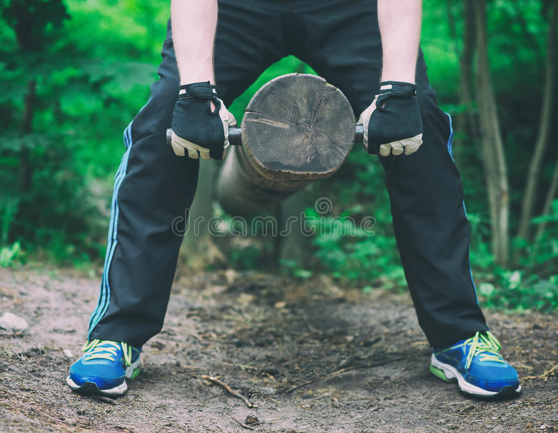 Man lifting log. Man lifting log in the forest stock images