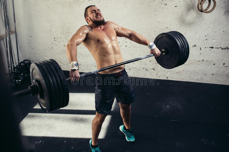 Man lifting weights. muscular man workout in gym doing exercises with barbell stock image