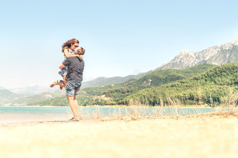 Man lifting woman in the air. Happy laughing couple on holiday. Mountain landscape. Boyfriend carrying girlfriend. Romantic moment royalty free stock images