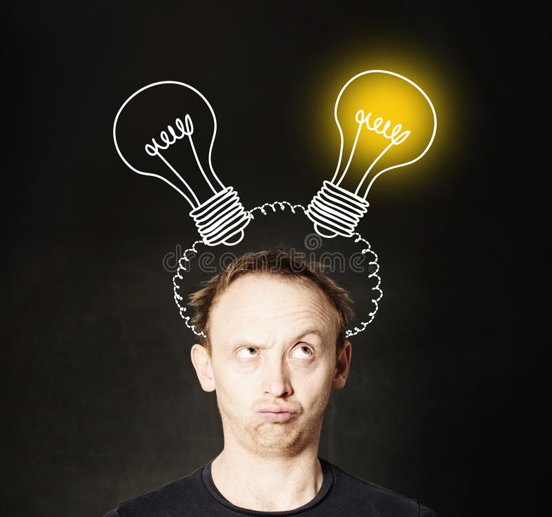 Man with light bulb on blackboard background. Brainstorming and idea concept royalty free stock image