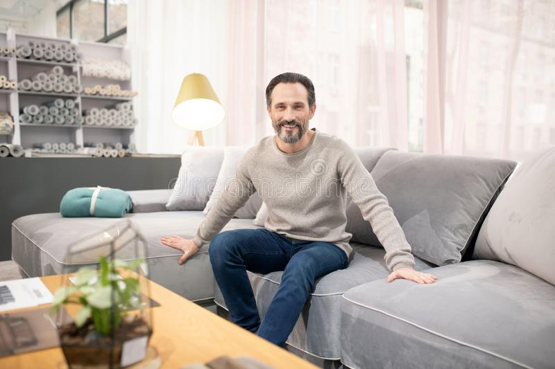 Man in light sweater and jeans feeling good stock photos