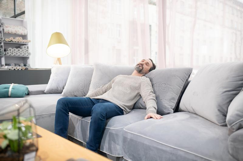 Man in light sweater and jeans feeling relaxed royalty free stock images