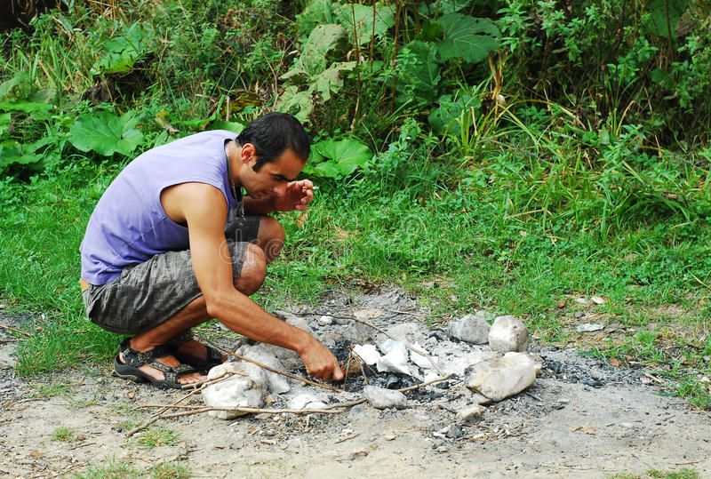 Man lighting fire stock photo
