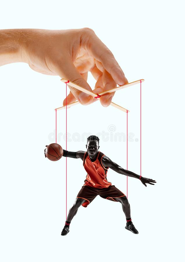 Man like a puppet in somebodies hands. Concept of manipulation. Man like a puppet in somebodies hands on blue background. Concept of unfair manipulation stock images