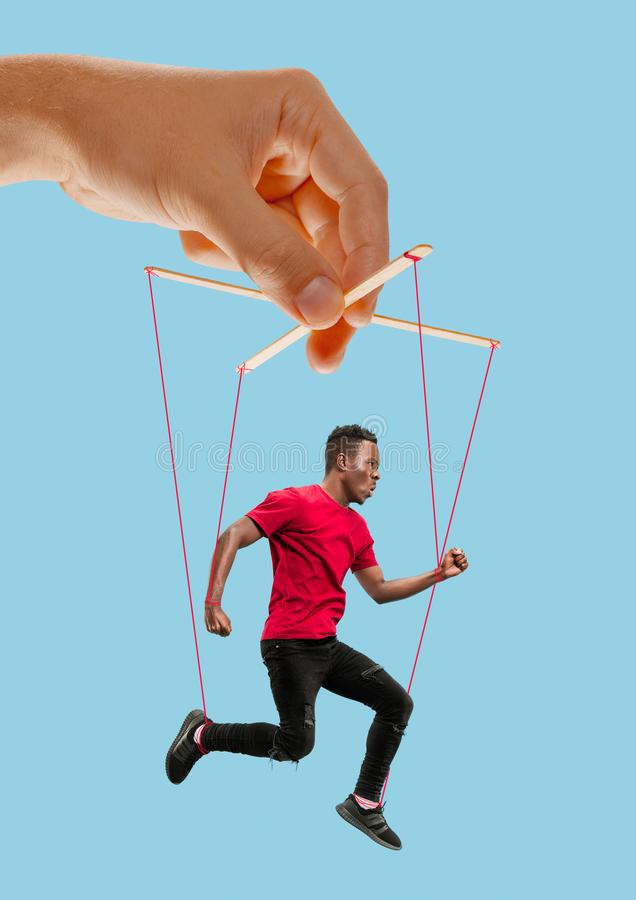Man like a puppet in somebodies hands. Concept of manipulation. Man like a puppet in somebodies hands on blue background. Concept of unfair manipulation stock image