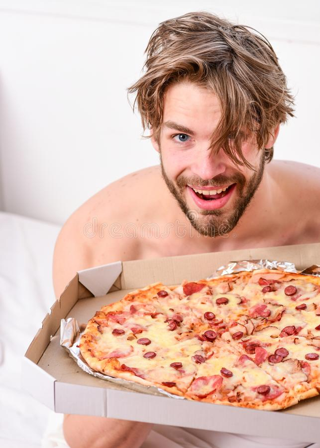 Man likes pizza for breakfast. man eat pizza lying on bed. Portrait of lazy muscular man eating pizza while laying royalty free stock image