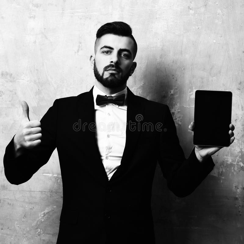 Man likes tablet. Young bearded speaker presents new pocket device and shows thumbs up. Old cracked beige background in. Vintage style and concept of gadgets stock image