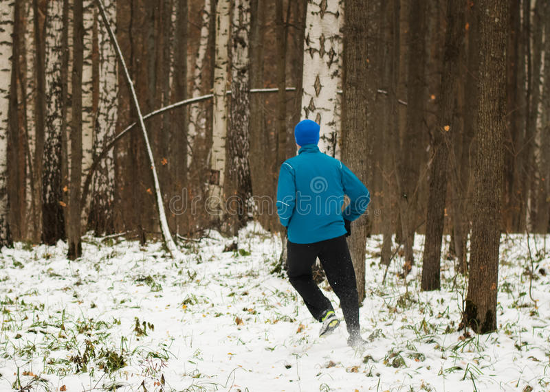 The man likes to run in the winter forest. stock photography
