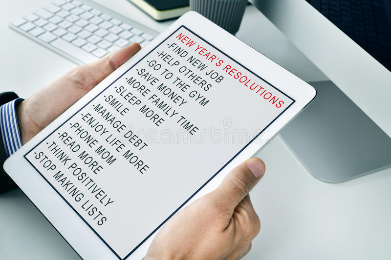 Man with a list of new years resolutions in a tablet. Closeup of a young caucasian businessman in his office observing his tablet computer with his list of new stock image