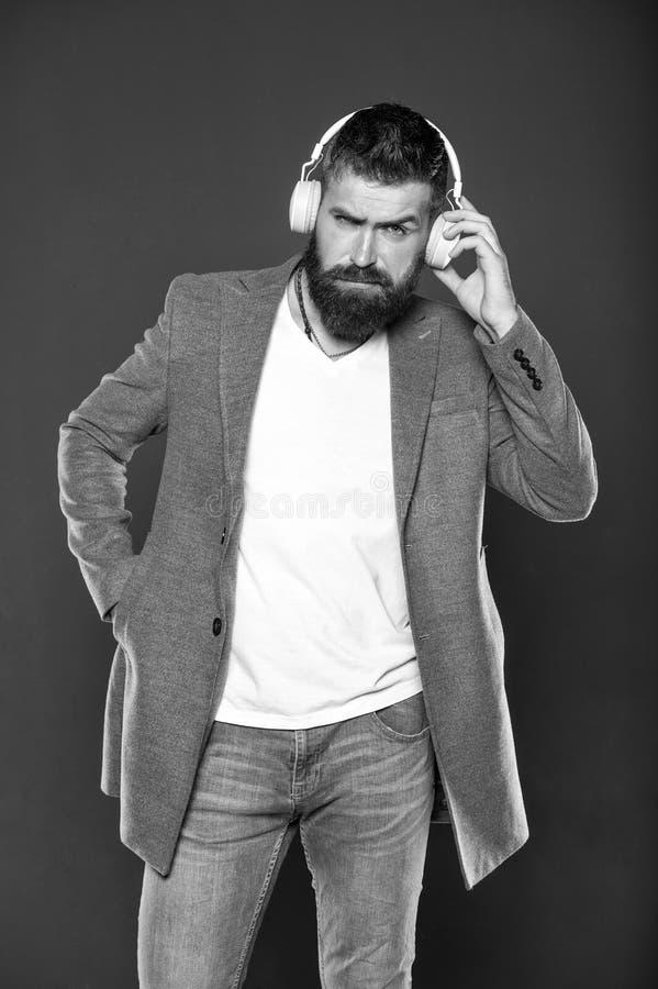 Man listening music wireless headphones. Hipster wear modern technology gadget headphones. Excellent sound. Music stock image
